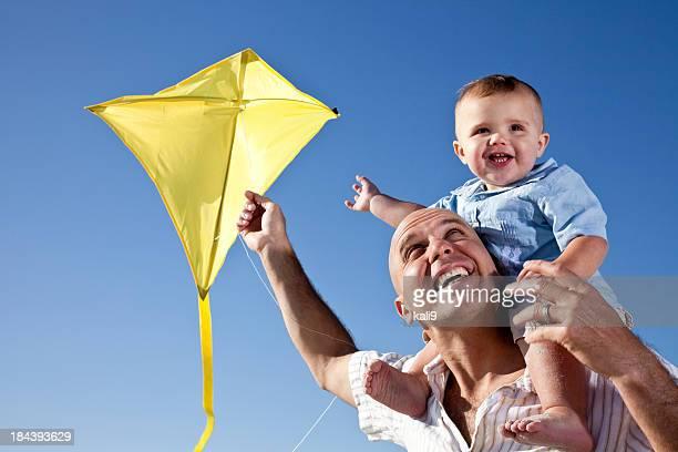 Pai com rapaz sobre os ombros voar kite