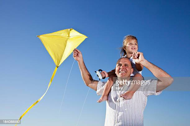 Father with little girl on shoulders flying kite