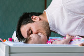 Father with newborn baby in bedroom