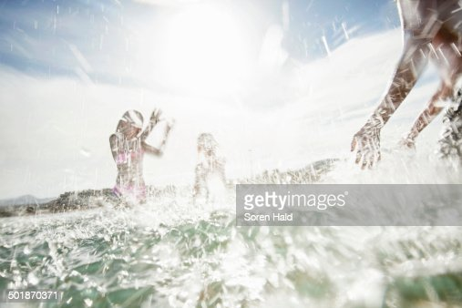 Father with son and daughter splashing each other on beach