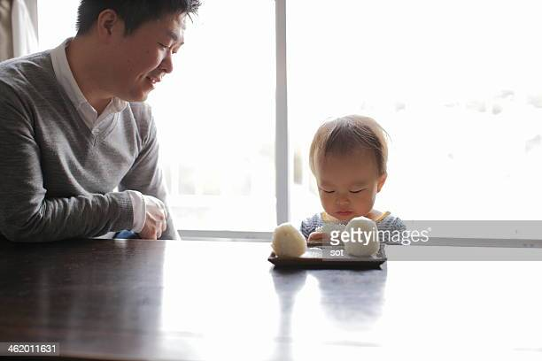 Father with son eating rice ball at table