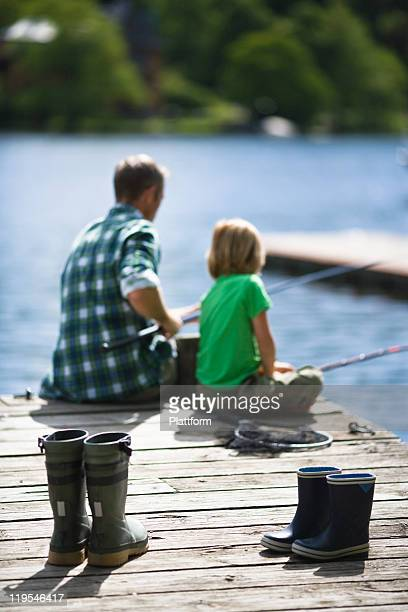 Father with son fishing, rubber boots on foreground