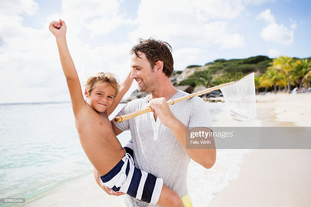Father with son (8-9) holding fishing net : Stock Photo