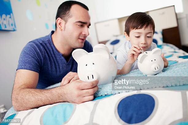 Father with son (4-5) holding piggybanks in bedroom