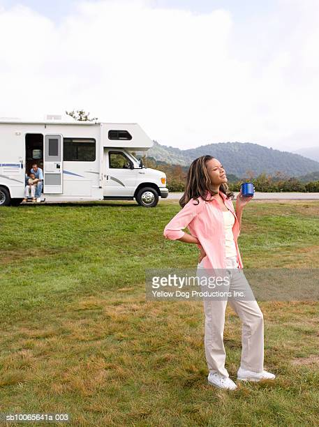 Father with son (12-13) in motorhome, woman drinking coffee in foreground