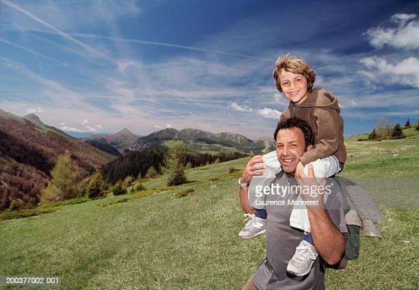 Father with son (8-10) on his shoulders smiling, portrait
