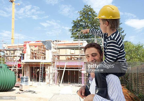 Father with son on shoulders at building shell