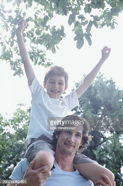 Father with son (9-11) on shoulders in backyard, portrait