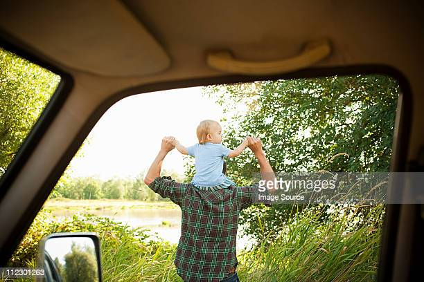 Father with son on shoulders, viewed from a car