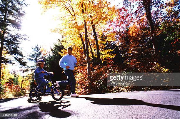 Father with son riding bicycle on road