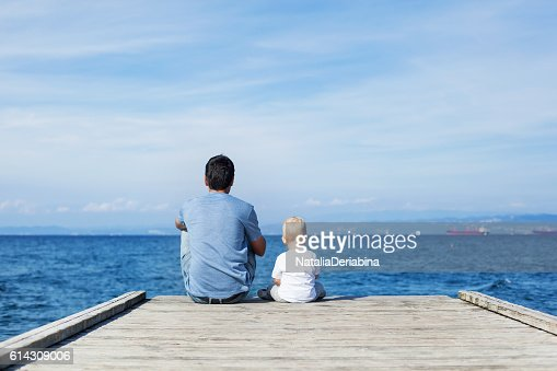 Father with son sitting on the sea pier : Stock Photo