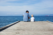 Father with son sitting on the sea pier. Family background. Lifestyle, Holidays and Travel concept. Parent and child together.