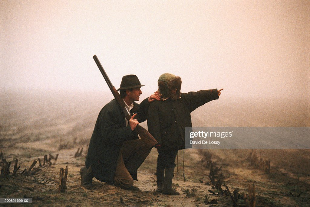 Father with son (4-5) standing outdoors, boy pointing