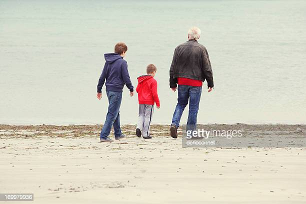 father with sons on the beach