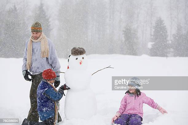 Father with two children (6-7) building snowman