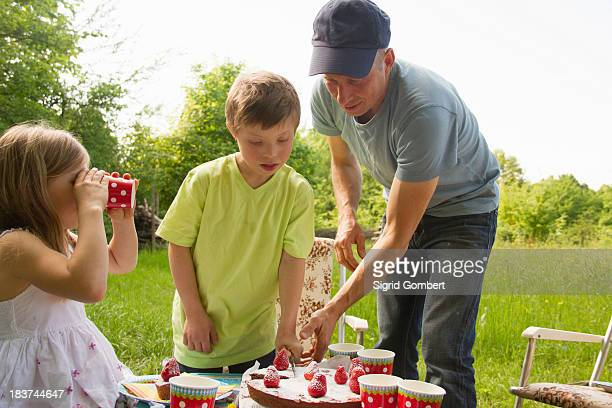 Father with two children cutting birthday cake outdoors