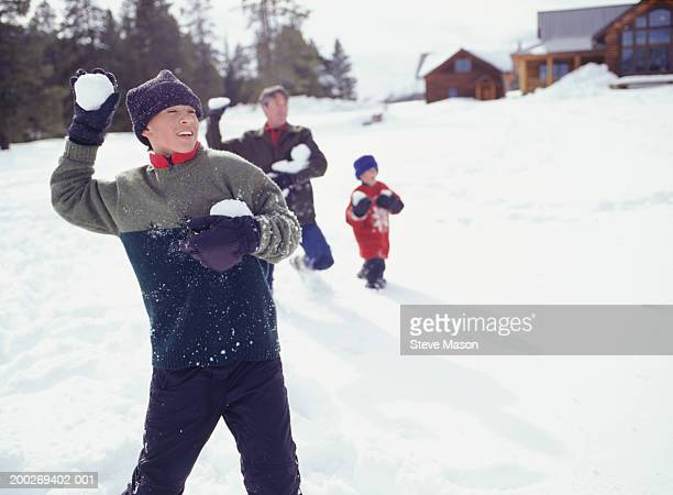 Father with two children (4-5), (14-15) having snowball fight