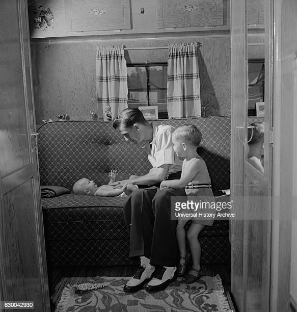 Father with Two Children in Trailer Home at Glenn L Martin Trailer Village a Farm Security Administration Housing Project Middle River Maryland USA...