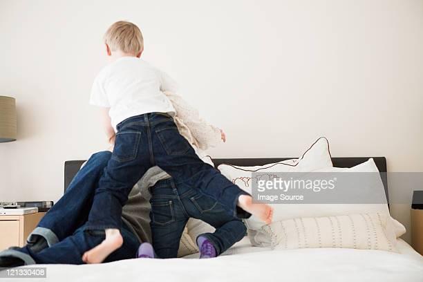 Vater mit zwei Kindern spielen auf Bett
