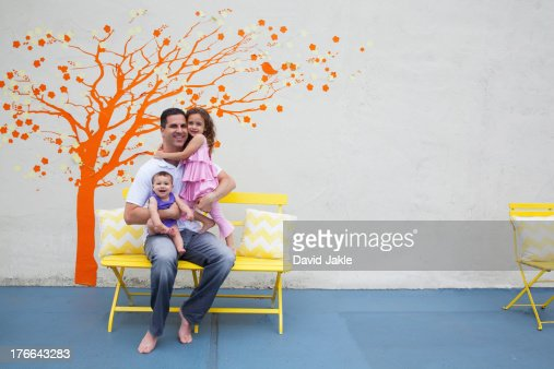 Father with two daughters in front of tree mural on wall