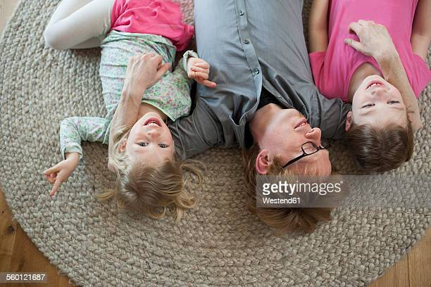 Father with two daughters lying on floor