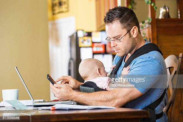 Father working from home office while taking care of baby