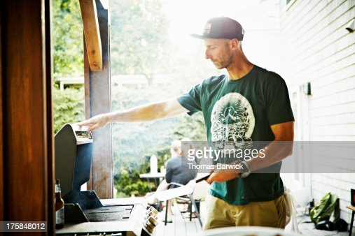 Father working on barbecue in backyard