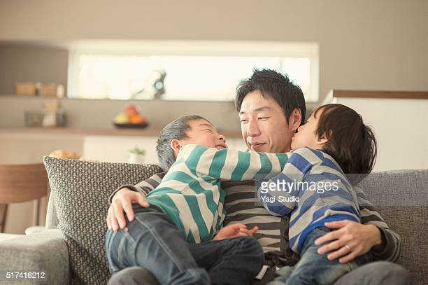 Fatherr and two sons  kissing and hugging at home