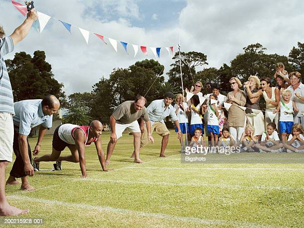 Fathers at starting line of running track on school sports day