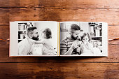 Fathers day composition. Photo album, black-and-white pictures. Studio shot on wooden background.