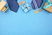 Fathers Day top border of gifts, ties and hearts on a blue background. Top view with copy space,