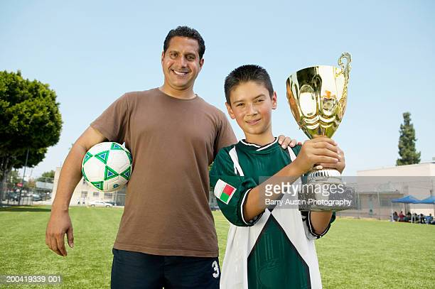 Father's hand on son's (7-9) shoulder, boy holding trophy, portrait