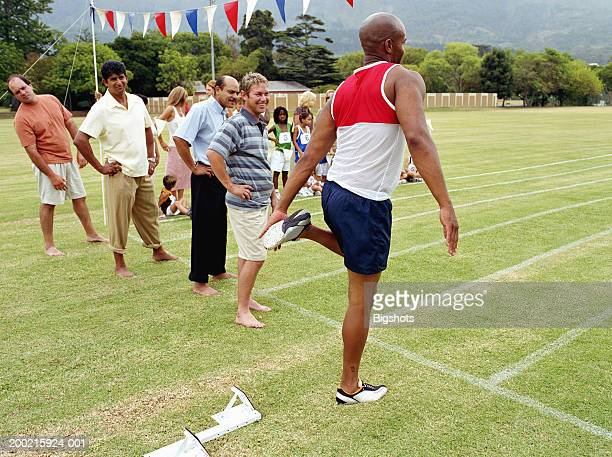 Fathers lining up at starting line at school sports day