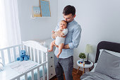 Father carrying baby son in bedroom