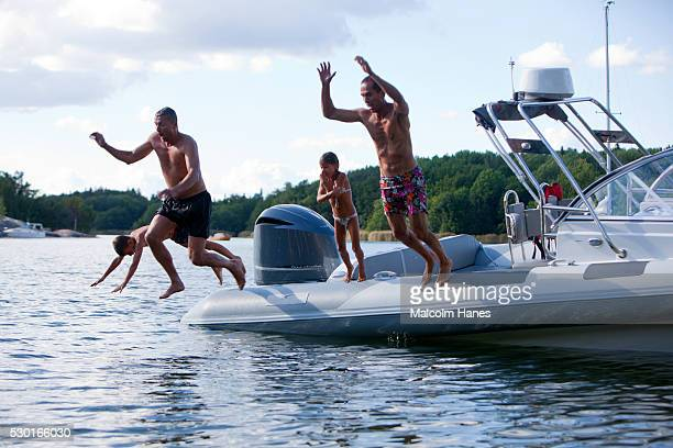Fathers with sons jumping into sea from motorboat