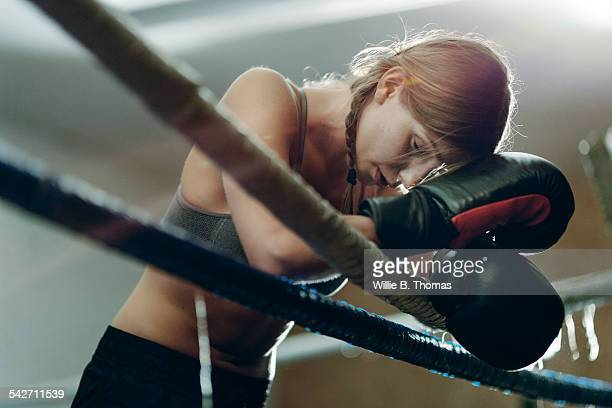 Fatigued boxer leaning ropes