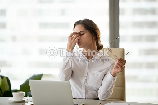 Fatigued businesswoman taking off glasses tired of computer work : Stock Photo
