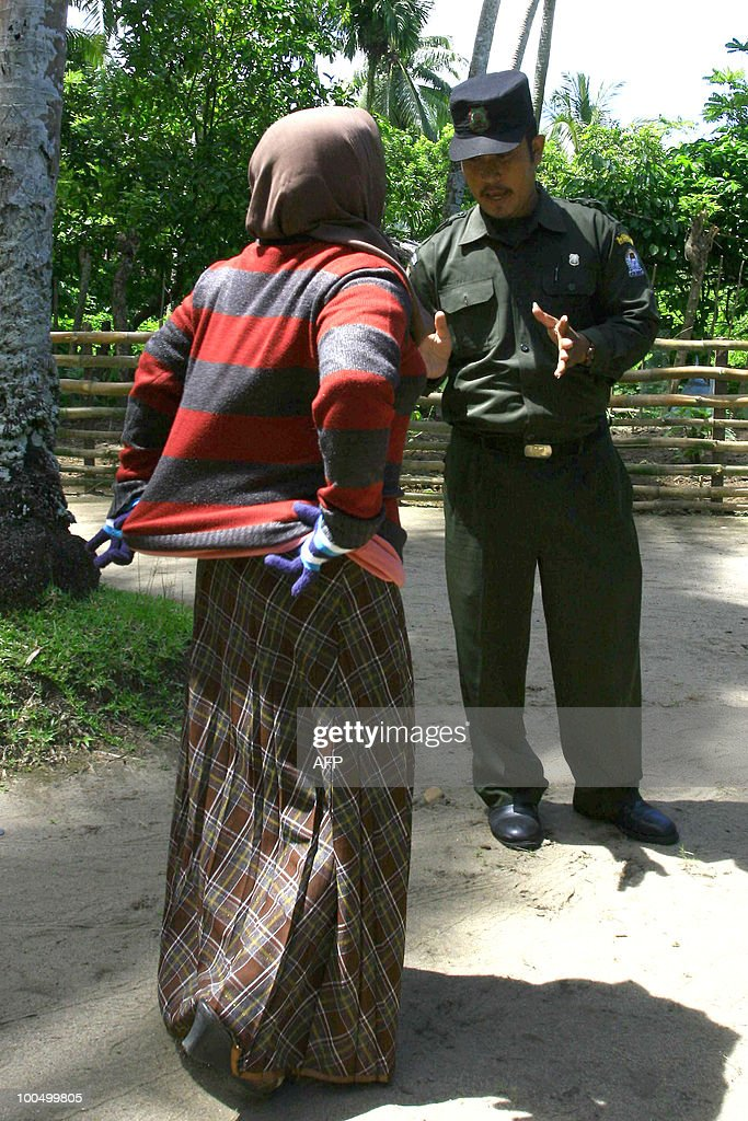 Fatima, a 40 year old Acehnese woman argues with an Islamic policeman after she was caught and made to change to 'acceptable' clothing in Lambalek village in West Aceh district of Aceh province during a campaign against women wearing tight pants and clothing in the district on May 25, 2010. Local authorities are implementing Sharia (Islamic) law, which has been adopted by the provincial government and which stipulates that women can only show their face and their hands, according to sharia police officials. Aceh province runs under special autonomy and is one of the most conservative regions in the mainly Muslim archipelago having established a religious police force.