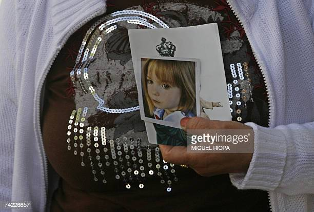 A woman carries a portrait of fouryearold Madeleine McCann at the Portuguese shrine of Fatima central Portugal 23 May 2007 The parents of Madeleine...