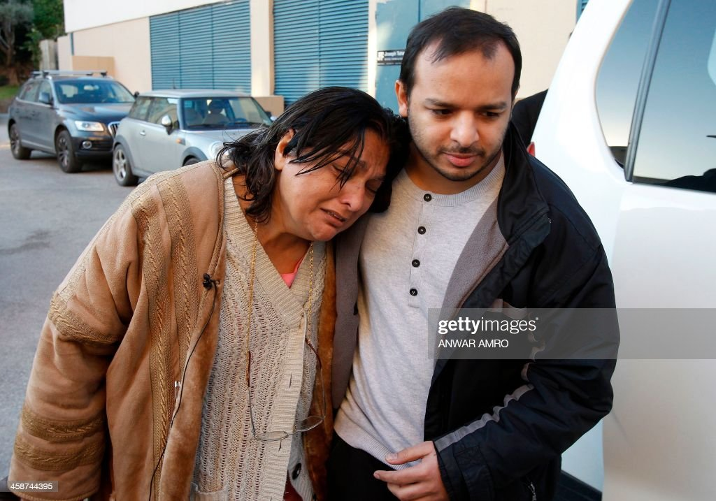Fatima, the mother of Abbas Khan, the British doctor who died in a Syrian jail, grieves with Abbas' brother outside the Hotel Dieu hospital in Beirut where the coffin of her son was brought from Syria by the Lebanese Red Cross on December 21, 213. The British government has held Damascus responsible for the death of the 32-year-old orthopaedic surgeon but Syrian authorities said that Khan was found 'hanging' in his cell, where he was being held for 'unauthorised activities,' and that he had committed suicide. AFP PHOTO / ANWAR AMRO