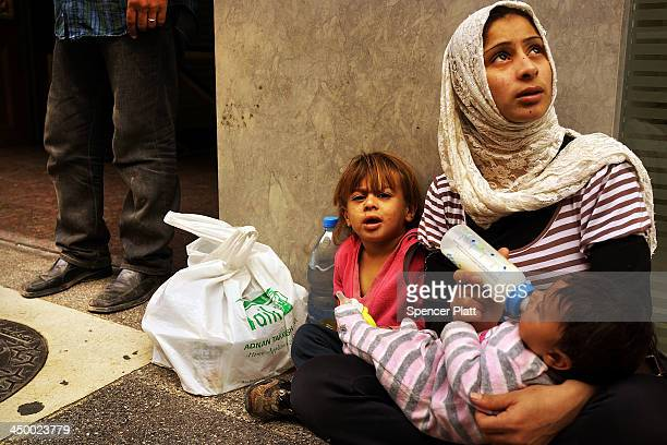 Fatma a Syrian woman from the city of Idlib begs with her two children in a wealthy district of Beirut on November 16 2013 in Beirut Lebanon As the...