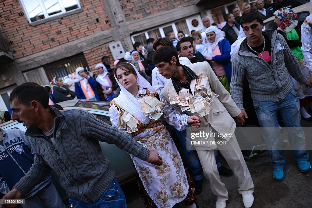Fatme Ulanova (2ndL), 20, and Djamal Sirakov, 23, dance with euro banknotes hung on their garnments as presents, during their two-day wedding ceremony in the village of Ribnovo, in southwestern Bulgaria, on January 2, 2013. The people of this Bulgarian mountain village are famous for performing their unique wedding ceremonies in winter time only. The inhabitants of the village of Ribnovo are Bulgarian-speaking Muslims, sometimes referred to as 'Pomaks' or 'people who have suffered'. Muslim Bulgarians are descendants of Christian Bulgarians who were forcibly converted to Islam by the Turks, during the 14th, 16th and the 18th century.