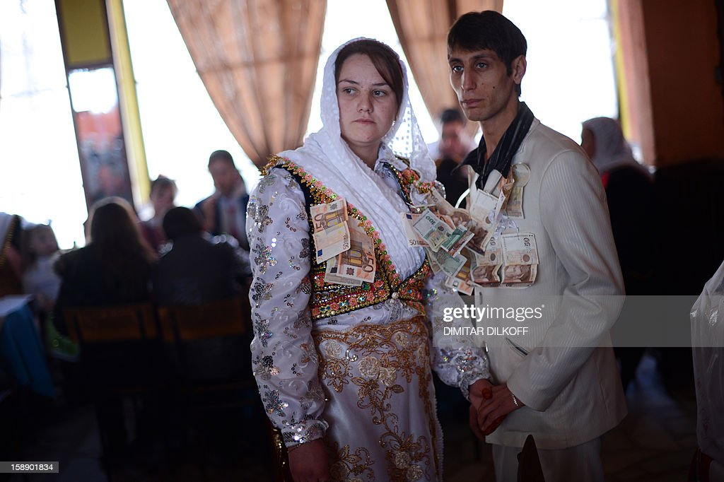 Fatme Ulanova (L), 20, and Djamal Sirakov, 23, stand with with euro banknotes hung on their garnments as presents during their two-day wedding ceremony in the village of Ribnovo, in southwestern Bulgaria, on January 2, 2013.The people of this Bulgarian mountain village are famous for performing their unique wedding ceremonies in winter time only. The inhabitants of the village of Ribnovo are Bulgarian-speaking Muslims, sometimes referred to as 'Pomaks' or 'people who have suffered'. Muslim Bulgarians are descendants of Christian Bulgarians who were forcibly converted to Islam by the Turks, during the 14th, 16th and the 18th century.