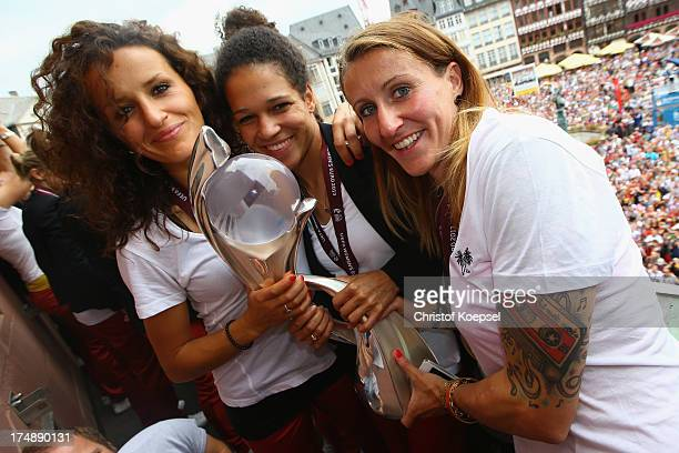 Fatmire Bajramaj Celia Okoyino da Mbabi and Anja Mittag of Germany lift the trophy after winning the UEFA Women's EURO 2013 on the balcony of the...