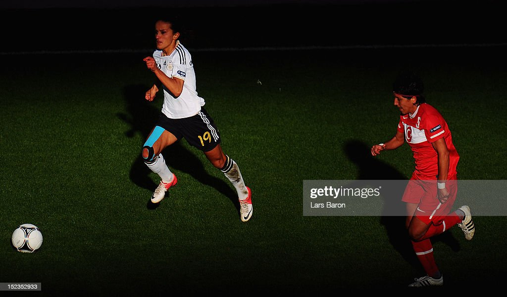 Fatmire Bajramaj of Germany runs with the ball next to Cigdem Belci of Turkey during the UEFA Womens Euro 2013 qualification match between Germany and Turkey at Schauinsland-Reisen-Arena on September 19, 2012 in Duisburg, Germany.