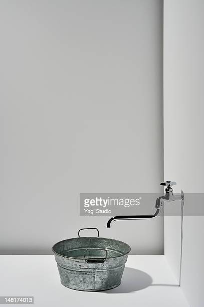 Faucet and pail on white background