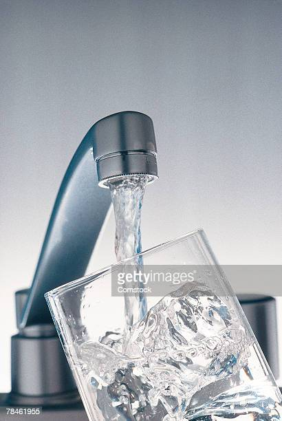 Faucet filling glass of ice with water