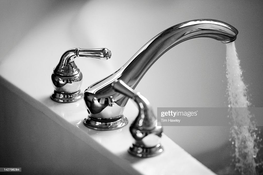 Faucet pouring water into bath tub : Stock Photo