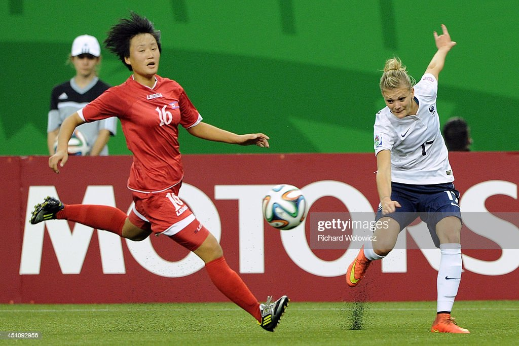 Faustine Robert of France passes the ball in front of Ri Un Yong of Korea DPR during the FIFA Women's U-20 3rd place game at Olympic Stadium on August 24, 2014 in Montreal, Quebec, Canada. France defeated Korea DPR