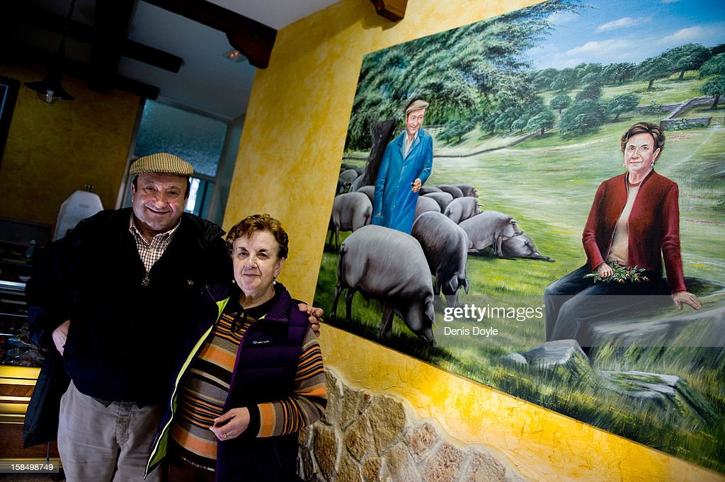 Faustino Prieto, owner of the small family-run Iberian ham business is photographed with his wife Candy Guerrero Jimenez beside a mural of themselves at their home in the village of Cespedosa on December 14, 2012 near Salamanca, Spain. Faustino runs a small family business rearing pure breed Iberian pigs and producing dry-cured Iberian ham or Jamon Iberico. Spaniards normally consume large quantities of their favoured Jamon Iberico and producers are hoping for improved sales over the busy holiday callender. The jamon legs are usually dry-cured for up to three years after the pigs have been few on a diet of acorns in the last three months of their lives.